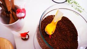 Vue supérieure de grains de café sur le fond blanc propre avec la composition des tasses de café, oiseaux colorés, lampes, jardin images stock