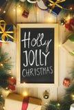 Vue supérieure de Holly Jolly Christmas Typography sur le tableau noir Surro photographie stock libre de droits