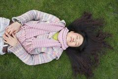 Vue supérieure de jeune femme asiatique avec de longs cheveux noirs se trouvant sur la pelouse Image stock