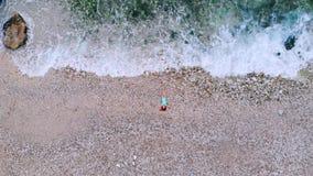 Vue supérieure de jeune femme se trouvant sur Pebble Beach près des vagues de mer banque de vidéos