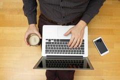 Vue supérieure de jeune homme causant en ligne avec des amis à l'aide de l'ordinateur portable Photos libres de droits