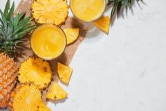 Vue supérieure de jus d'ananas frais dans le verre avec l'ananas franc Image stock