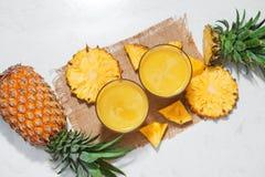 Vue supérieure de jus d'ananas frais dans le verre avec l'ananas franc Photos stock