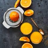 Vue supérieure de jus d'orange frais dans le presse-fruits grand en verre et d'agrume sur le fond concret foncé images libres de droits