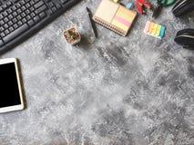 Vue supérieure de Keybroad avec le comprimé, l'écouteur, le carnet, le cactus et les fournitures de bureau sur le fond gris grung Images stock