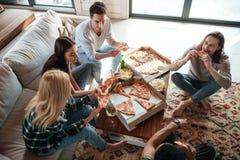 Vue supérieure de l'ami cinq mangeant de la pizza dans la maison Photo libre de droits