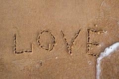 Vue supérieure de l'amour de mot écrite sur la plage de sable avec la vague de la mer Images stock