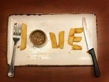 Vue supérieure de l'amour de mot du plat avec un couteau et d'une fourchette sur une table en bois Photo libre de droits