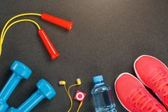 Vue supérieure de l'article de sport, des haltères, d'une corde à sauter, d'une bouteille de l'eau, des espadrilles et d'un joueu Photographie stock