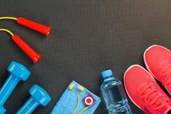 Vue supérieure de l'article de sport, des haltères, d'une corde à sauter, d'une bouteille de l'eau, des espadrilles et d'un joueu Photos stock