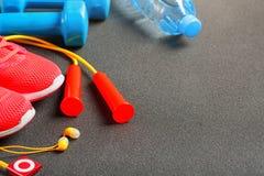 Vue supérieure de l'article de sport, des haltères, d'une corde à sauter, d'une bouteille de l'eau, des espadrilles et d'un joueu Image stock
