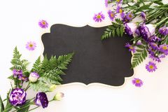 Vue supérieure de la belle disposition de fleurs pourpre et du tableau noir vide au-dessus du fond en bois blanc Copiez l'espace Image stock