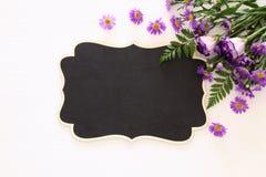 Vue supérieure de la belle disposition de fleurs pourpre et du tableau noir vide au-dessus du fond en bois blanc Copiez l'espace Photographie stock libre de droits