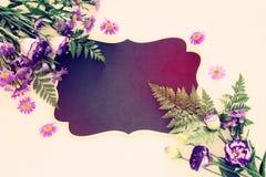 Vue supérieure de la belle disposition de fleurs pourpre et du tableau noir vide au-dessus du fond en bois blanc Copiez l'espace Photo stock