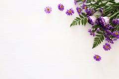Vue supérieure de la belle disposition de fleurs pourpre sur le fond en bois blanc Copiez l'espace Images stock