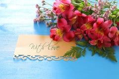 Vue supérieure de la belles disposition et lettre de fleurs rouges au-dessus du fond en bois bleu Image libre de droits