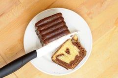 Vue supérieure de la coupe délicieuse de gâteau marbré de chocolat avec un petit morceau Image libre de droits