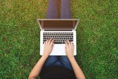 Vue supérieure de la jeune femme à l'aide de l'ordinateur portable sur une herbe photos stock
