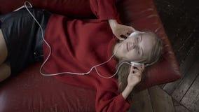 Vue supérieure de la jeune femme attirante dans des écouteurs écoutant la musique et souriant tout en se trouvant sur le divan à  banque de vidéos