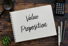 Vue supérieure de la loupe, de la calculatrice, de l'usine, du stylo et du carnet écrits avec la proposition de valeur photo libre de droits