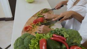 Vue supérieure de la planche à découper à la table de cuisine La femme remet découper des moitiés en tranches de poivron vert et  clips vidéos