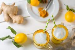Vue supérieure de latte de safran des indes ou de lait d'or en verres et citrons sur une table blanche photographie stock