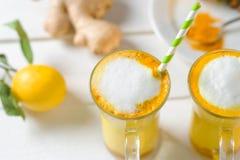 Vue supérieure de latte de safran des indes ou de lait d'or en verres et citrons sur une table blanche photo libre de droits