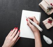 Vue supérieure de lettre de Noël Main femelle écrivant une lettre sur le fond noir avec des cadeaux de Noël Photos libres de droits