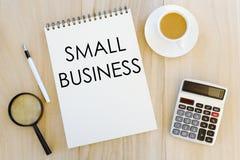 Vue supérieure de loupe, de stylo, d'une tasse de café, de la calculatrice et du carnet écrits avec la petite entreprise sur le f images libres de droits