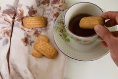 Vue supérieure de main de femme tenant les biscuits, tasse de thé chaude sur la table Images stock