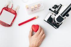 Vue supérieure de main tenant le coeur rouge contre des fioles avec le sang et le microscope photo libre de droits