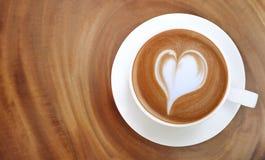 Vue supérieure de mousse chaude de forme de coeur d'art de latte de café sur la table en bois image libre de droits