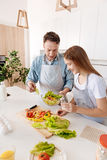 Vue supérieure de père gai et de fille faisant cuire la salade Photos stock
