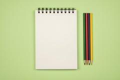 Vue supérieure de page vide de carnet avec les crayons colorés Image libre de droits