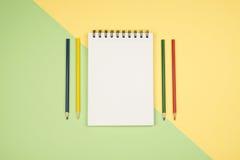 Vue supérieure de page vide de carnet avec les crayons colorés Photographie stock libre de droits