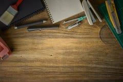 Vue supérieure de papier blanc et fournitures scolaires sur le bois foncé Images stock