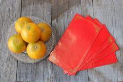 Vue supérieure de paquet rouge d'enveloppe ou patte et oranges d'ANG dans une cuvette sur le vieux fond en bois Concept chinois d Image libre de droits