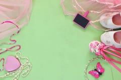 Vue supérieure de petit équipement de partie de filles : fleurs blanches de chaussures, de couronne et de baguette magique à côté photos stock