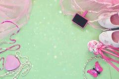Vue supérieure de petit équipement de partie de filles : fleurs blanches de chaussures, de couronne et de baguette magique à côté photographie stock