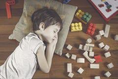 Vue supérieure de petit garçon avec les yeux fermés se trouvant sur le plancher en bois et beaucoup de jouets colorés autour de l Photos stock