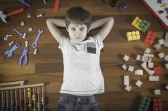 Vue supérieure de petit garçon se trouvant avec des mains derrière sa tête sur le plancher en bois et beaucoup de jouets colorés  Images libres de droits