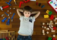 Vue supérieure de petit garçon se trouvant avec des mains derrière sa tête sur le plancher en bois et beaucoup de jouets colorés  Photographie stock