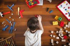 Vue supérieure de petit garçon se trouvant sur le plancher en bois et jouant avec les jouets colorés Image libre de droits