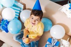 Vue supérieure de petit garçon tenant le petit pain d'anniversaire Photos stock