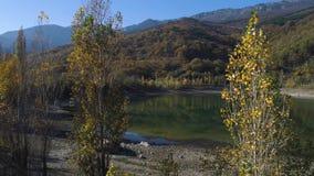 Vue supérieure de petit lac avec la réflexion des montagnes en automne projectile Belle vue avec la réflexion de coloré clips vidéos