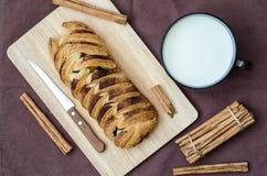 Vue supérieure de petit pain avec les bâtons de cannelle et la tasse de lait Photo stock