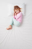 Vue supérieure de petite fille dormant dans la pose de foetus Photographie stock