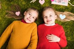 vue supérieure de petites soeurs heureuses se trouvant sur le tapis entouré Photos libres de droits