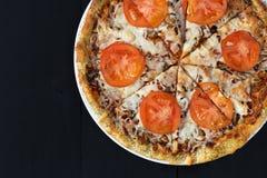 Vue supérieure de pizza coupée en tranches sur un fond en bois noir images stock