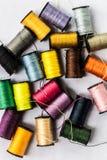 Vue supérieure de plan rapproché des bobines colorées avec des fils de couture sur le fond blanc Images stock
